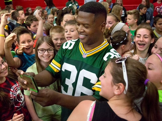 LeRoy Butler is surrounded by students at Bay Lane Middle School in Muskego after a presentation in 2016.