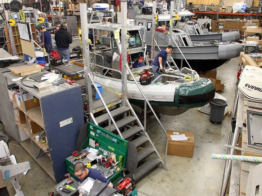 Employees work on rigging a boat's electronics at Safe Boats in Bremerton on Tuesday May 01, 2012. (MEEGAN M. REID/KITSAP SUN)