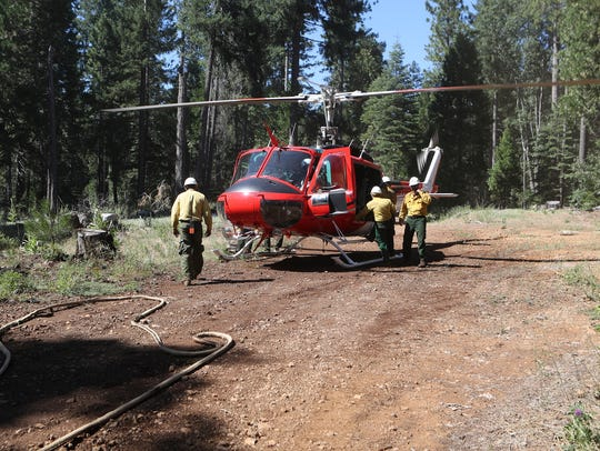 U.S. Forest service firefighters break down a helicopter