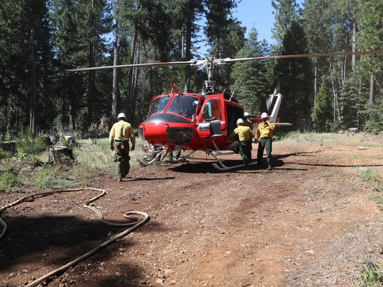 U.S. Forest service firefighters break down a helicopter as crews get a handle on several small fires Monday east of Shingletown.