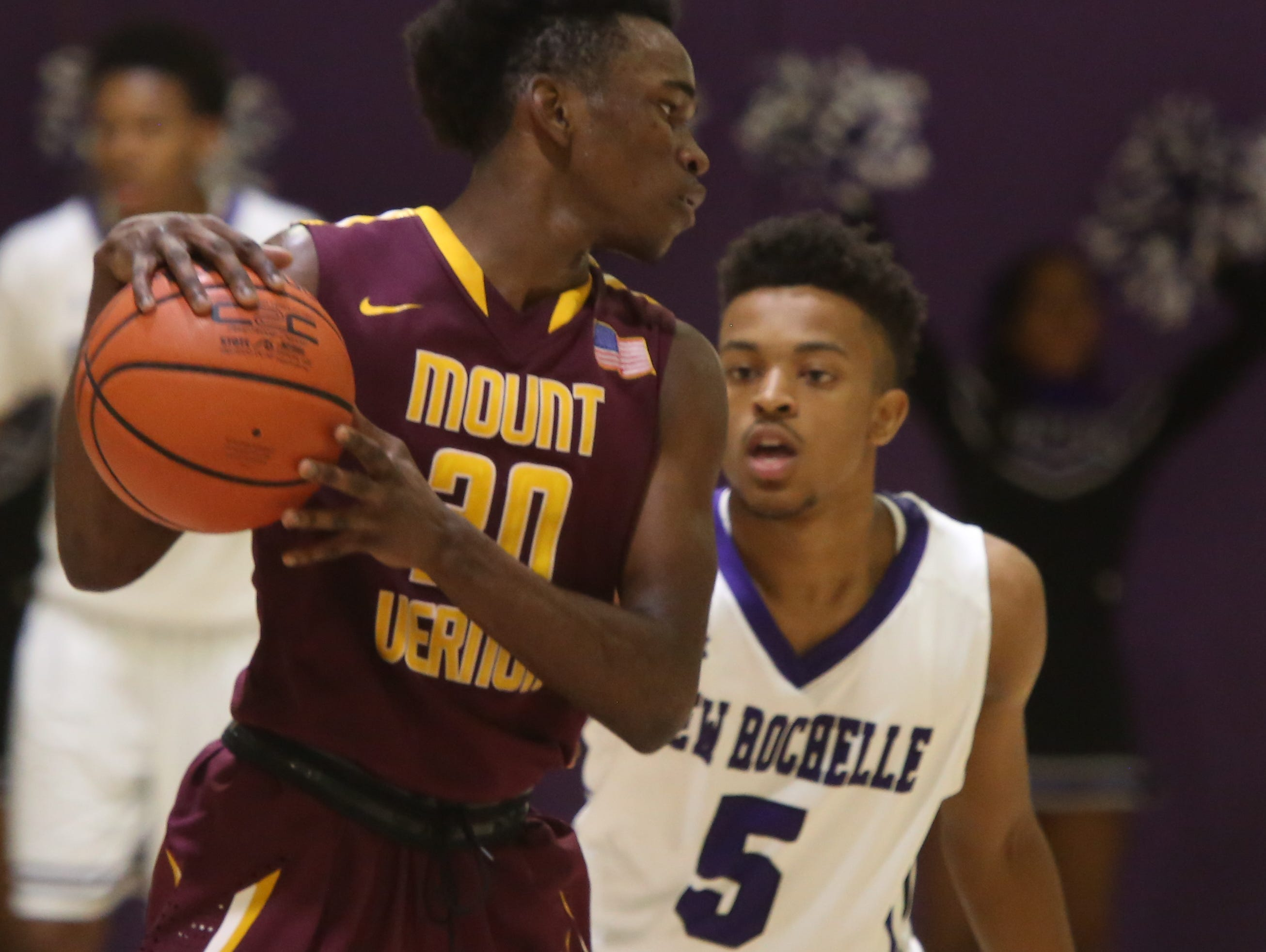 Tyeshon Marton (5) of New Rochelle guards Marco Morency (20) of Mount Vernon during game action at New Rochelle High School on Jan 4, 2016. Mount Vernon defeated New Rochelle 72-63.