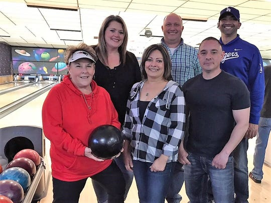 Village Manager Debi Lee, front left, and Deputy Manager Ron Sena, front right, knocked down some pins.