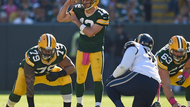 Packers quarterback Aaron Rodgers calls signals at the line of scrimmage against the Rams.