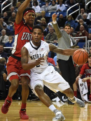 Nevada's Tyron Criswell dribbles toward the basket with UNLV's Patrick McCaw covering him Tuesday at Lawlor Events Center.