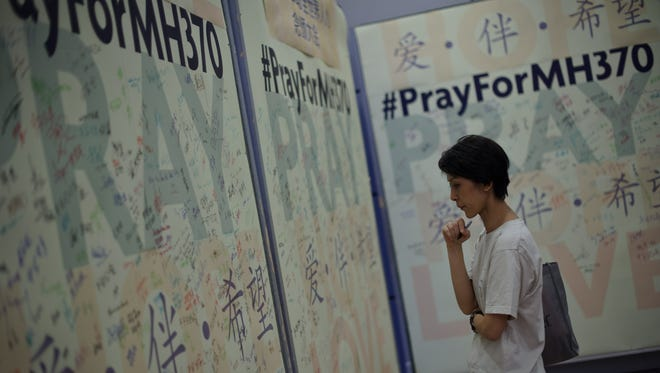 A woman reads prayers and well-wishes on a wall for passengers aboard missing Malaysia Airlines Flight MH370 during a mass prayer in Kuala Lumpur on April 6.