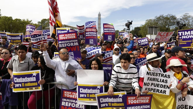 People are given U.S. flags as they rally in support of immigration reform Tuesday on The National Mall in Washington D.C.
