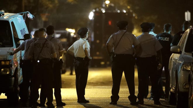 Policer officers watch as a gunman is apprehended following a standoff Wednesday, Aug. 14, 2019, in Philadelphia. A gunman who opened fire on police Wednesday as they were serving a drug warrant in Philadelphia, wounding several officers and triggering a standoff that extended into the night, is in police custody, authorities said. (AP Photo/Matt Rourke)
