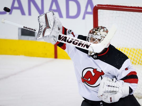 New Jersey Devils goalie Keith Kinkaid swats away the