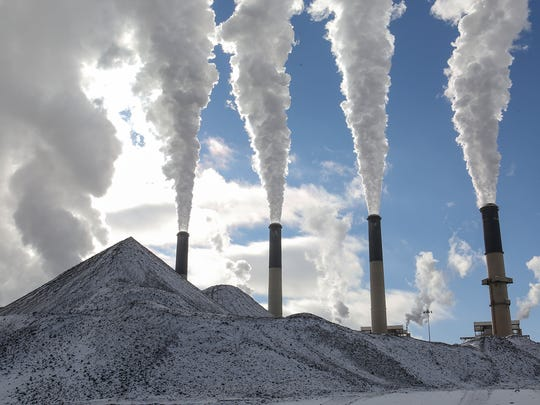 Large stacks fill the sky with steam at PacifiCorp's Jim Bridger coal plant in southwestern Wyoming on Dec. 7, 2016. In the foreground, snow covers piles of coal.