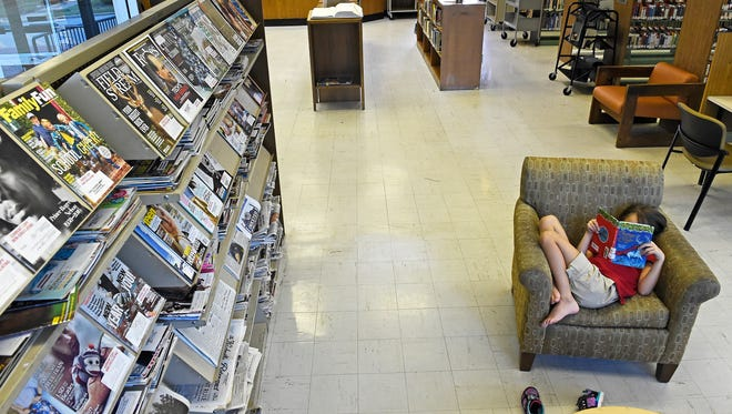 Eight-year-old  Ava Barnett gets comfortable after finding a book to read inside the Donelson Library.