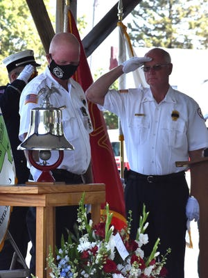 """Keith """"Doc"""" Patterson, commander of the Southeast Iowa Regional Honor Guard, saw that traditions of the fire service were honored during the funeral of Osco-Andover fire chief Roger Stancliff on Saturday morning, Sept. 5, in Andover Lake Park. Among the traditions was the ringing of a bell by firefighter Pete Neeld, left, while firefighter Tom Gainey salutes. In the fire service, bells call firefighters to service and also mark their return to quarters when the fire has been put out."""