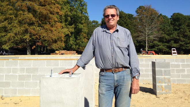 Phil Shipe stands Friday beside the foundation of a home his company, Shipe Builders, is building off Union Church Road near Salisbury. It was one of several permit applications he submitted in June before a new fire sprinkler regulation took effect.