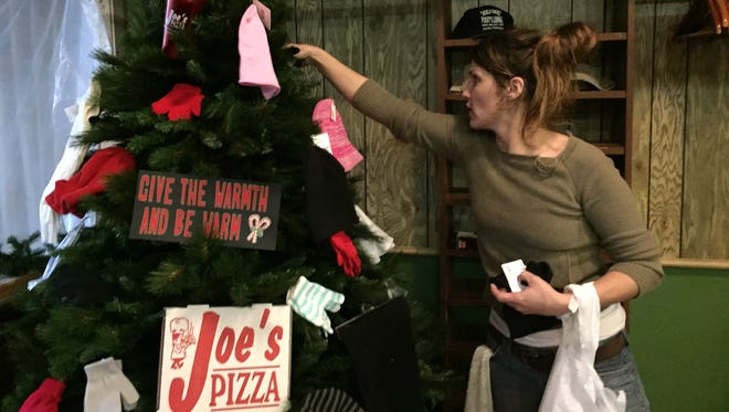 Abby Davis, manager at Joe's Pizza, adds a donation of hats and gloves to the tree.
