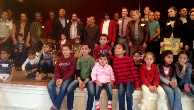 Syrian families in Clarkston attend a welcome event with Mayor Ted Terry, center, Congressman Hank Johnson, center left, and other community leaders.