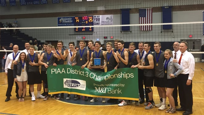 The Northeastern boys' volleyball team poses with the District 3 2-A championship trophy, its fifth consecutive title. The Bobcats defeated York Suburban in three games.