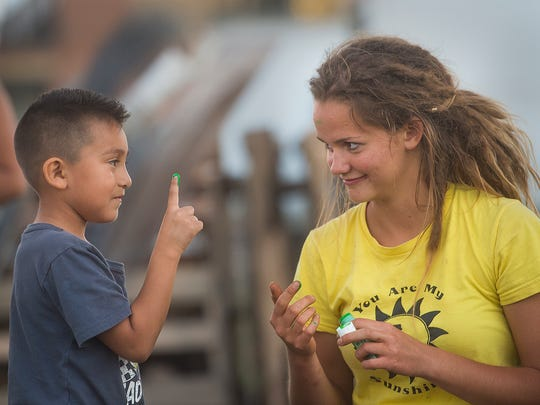 Dylan Lopez, 5, jokes around with student coordinator Mary Margaret Blum at Painted Turtle Farm on Aug. 29, 2016.