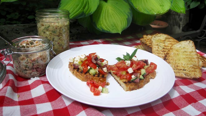 This Sunday, May 22, 2016 photo, shows salmon salad in a jar, left, next to the white bean salad and chopped greek salad on grilled bread in New York. This recipe spells out three different toppings, all vaguely Mediterranean: a white bean salad with fresh fennel thickened with mashed beans so that the filling sticks to the bread; smoked salmon rillettes, finely-chopped salmon flavored with capers, lemon and fresh herbs and bound with sour cream; and a chopped Greek salad.