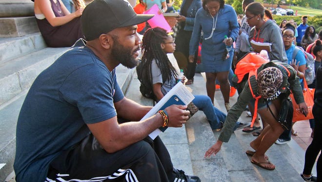 A.D. Carson, who earned a doctoral degree in rhetorics, communication and information design in 2017 from Clemson University, sits after leading a march from the back of Sikes Hall to the front steps. organizer D.J. Smith, Ian Anderson , Me'khayla Williams and Rae-Nessa White were also part of the five given a citation for trespassing in the administration building, according to Sherman Jones, another student organizer. Students protested over exclusion, racial insensitivity, and administrative inaction at the university in 2016.