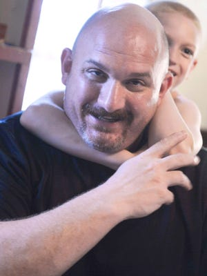 Nine-year-old Cody Curkendall puts a sleeper hold on his dad, Pete, in their Liverpool, N.Y., home.