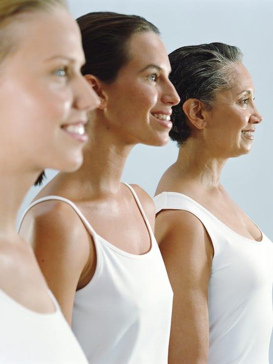 Three women smiling, side view