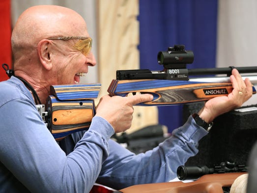 Ken Tarrant of Virginia Beach lets out a big laugh after shooting an Anschutz 8002 CMP Air Rifle with a large compressed-air cylinder allows 300 shots of .177 pellets per charge at the Convention Center on Thursday, April 24, 2014.