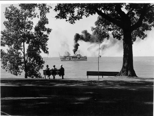 A group watches a steamboat, which was the way to travel in the late 1800s and early 1900s, cruise by Lakeside Chautauqua. Lakeside has been a popular family destination for more than a century.