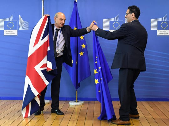 Members of protocol adjust the British and EU flags prior to the arrival of British Prime Minister David Cameron at EU headquarters in Brussels on June 28.