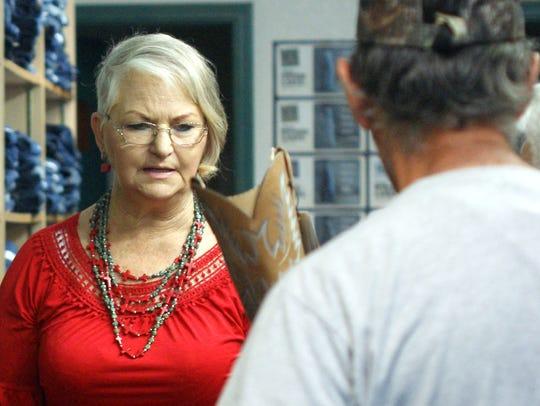 Diana Chadborn helps a customer at the boot rack. Circle