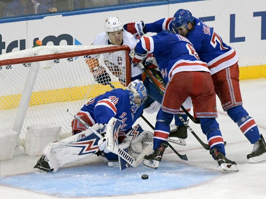New York Rangers goaltender Alexandar Georgiev (40) stops the puck as Rangers' Jacob Trouba (8) and Brady Skjei (76) defend against New York Islanders left wing Anders Lee (27) during the third period of an NHL preseason hockey game Tuesday, Sept. 24, 2019, at Madison Square Garden in New York. (AP Photo/ Bill Kostroun)