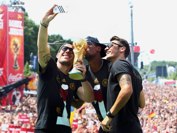 Lukas Podolski, Jerome Boateng and Mesut Ozil pose for a selfie with the World Cup trophy.