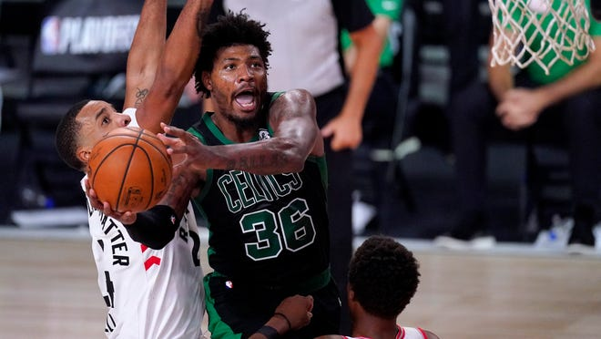 The Celtics' Marcus Smart (36) goes up for a shot against the Raptors' Norman Powell, left, and Kyle Lowry during the second half of Game 7 Friday night.