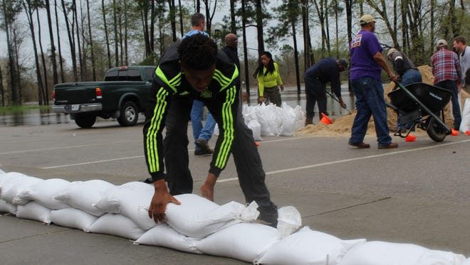 Orrion Bailey lays down sandbags Saturday outside Ebenezer Missionary Baptist Church on East Eighth Street in Hattiesburg as rising floodwaters began to threaten the church.