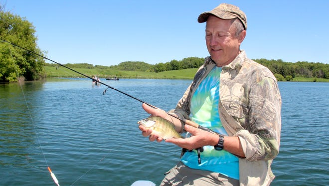 Kal Larson of Brookfield, Wis. holds a bluegill caught while fishing at Blackhawk Lake near Cobb, Wis.