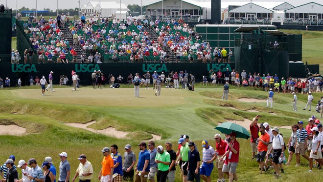 Large crowds dealt with the heat Monday as they followed golfer Jordan Spieth and others on the 9th green during the first day of practice for the  2017 U.S. Open  Championship at Erin Hills.