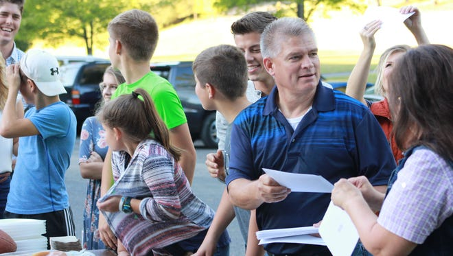 "Gil Bates hands out a stack letters during a family picnic on ""Bringing Up Bates."""