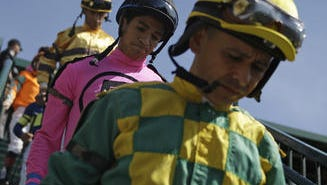 Jockeys walk into the paddock before a race before the 140th running of the Kentucky Derby horse race at Churchill Downs Saturday in Louisville, Ky.
