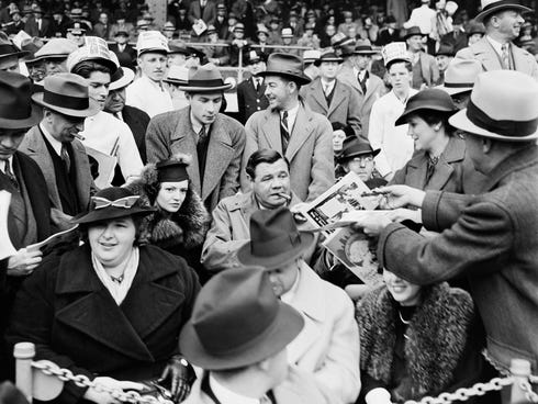 A man hands a program to baseball legend Babe Ruth, center, as he is joined by his second wife Clare.
