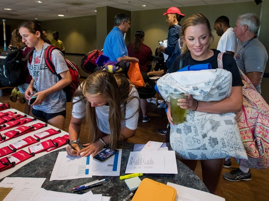 Alabama Christian Academy softball player Lacey Spear, right, signs in as high school athletes arrive at the Auburn Montgomery campus in Montgomery, Ala. for the AHSAA All-Star Sports Week on Monday July 17, 2017.
