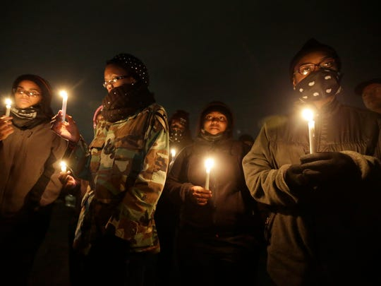 Young women attend a candlelight vigil for victims