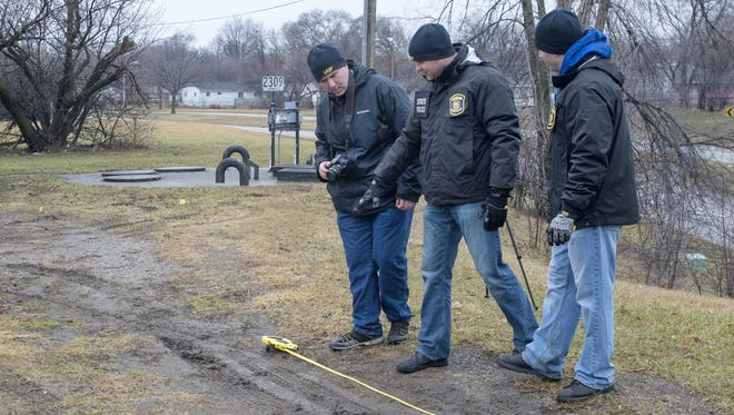 Michigan State Police Detective Troopers, from left, Joe McMillan, Don Pisha and Bryant Greenert measure tire tracks on Tuesday, Jan 24, 2017, near the scene of the shooting of Demarlon Thomas, 31, in Saginaw the previous evening.