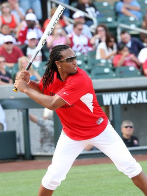 Arizona Cardinal Larry Fitzgerald takes a swing in the 2014 Larry Fitzgerald Celebrity Softball Game.