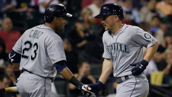 Seattle Mariners' Kyle Seager, right, celebrates with Nelson Cruz after hitting a solo home run during the sixth inning of a baseball game against the Chicago White Sox, Friday, Aug. 28, 2015, in Chicago.