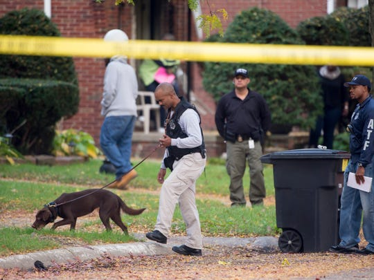 An Alcohol Tobacco and Firearms agent uses a canine to investigate the crime scene where Detroit Police said a gang related incident left five people shot including a toddler who died.