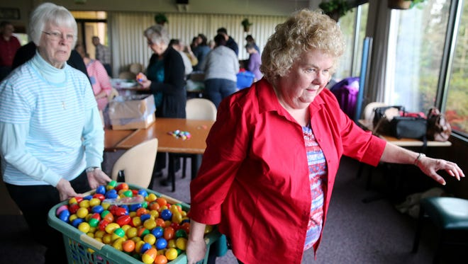 Volunteers Dianne Altenburg, left,  and Patti Prichard carry a basket of plastic Easter eggs at the Bremerton Elks Lodge on Tuesday. Lodge members prepared thousands of eggs - both plastic and chicken - for Sunday's egg hunt, which is scheduled for 1:30 to 2:30 p.m. Sunday at Bremerton Elks Lodge BPOE 1181, 4131 Pine Road.