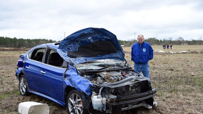 Stephen Wilkinson, warning coordination meteorologist with the National Weather Service, looks at a damaged car after severe weather hit Lamar County Tuesday afternoon.  It was confirmed that an EF2 twister touched down in the county near Sones Road.
