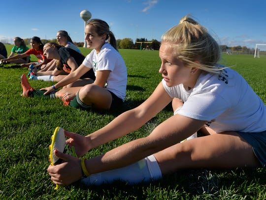 Sauk Rapids-Rice High School freshman forward Chloe Stockinger stretches with teammates at the start of practice Wednesday at the school.