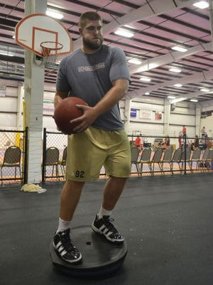 Drew Nowak keeps his balance while lifting a 15-pound medicine ball in an agility drill during a workout at House of Speed training facility in Ashwaubenon.