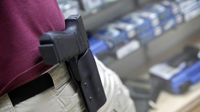 An employee with a holstered .45 handgun stands behind the counter Tuesday, April 6, 2010, at Caswells Shooting Range in Mesa, Ariz.