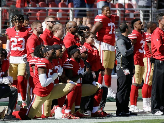 San Francisco 49ers players kneel during the performance
