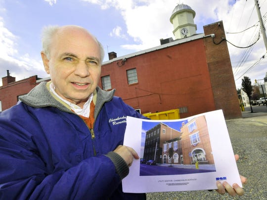 Alllen Coffman, Chambersburg Borough Council president, holds the plans for Borough Hall expansion Tuesday, Nov. 24, 2015, as he stands in the now vacant lot along Queen Street. Two houses beside Borough Hall were demolished to make way for the expansion.